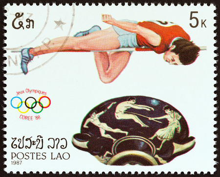 olympic sports: LAOS - CIRCA 1987: A stamp printed in Laos from the Olympic Games, Seoul. Sports and Greek Pottery  issue shows High jumping and bowl with handles, circa 1987. Editorial