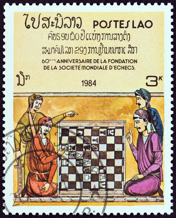 estampilla: LAOS - CIRCA 1984: A stamp printed in Laos from the 60th Anniversary of World Chess Federation  issue shows Four men at chessboard illustration from King Alfonso Xs Book of Chess, circa 1984.