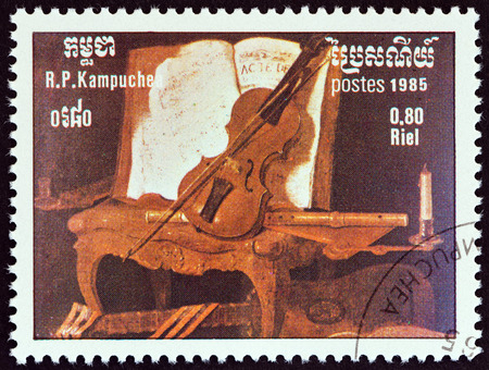 estampilla: KAMPUCHEA - CIRCA 1985: A stamp printed in Kampuchea from the International Music Year  issue shows Still Life with Violin, Flute and Guitar by Jean-Baptiste Oudry, circa 1985.
