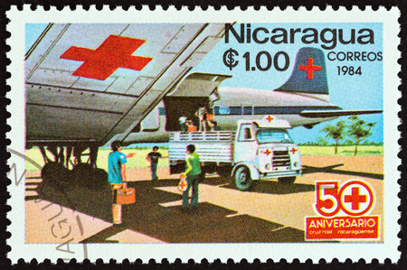 timbre: NICARAGUA - CIRCA 1984: A stamp printed in Nicaragua from the  50th anniversary of Nicaraguan Red Cross  issue shows Red Cross airplane and ambulance, circa 1984. Editorial