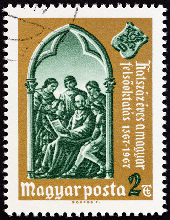 magyar posta: HUNGARY - CIRCA 1967: A stamp printed in Hungary issued for the 600th anniversary of Higher Education in Hungary shows teaching in 14th century class, circa 1967. Editorial