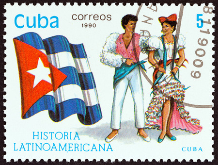estampilla: CUBA - CIRCA 1990: A stamp printed in Cuba from the Latin American History 5th series issue shows Flag and Traditional Costumes Cuba, circa 1990.