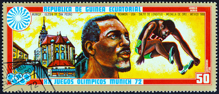 medalist: EQUATORIAL GUINEA - CIRCA 1972: A stamp printed in Equatorial Guinea from the Olympic games, Munich issue shows Bob Beamon and St. Peters Church, circa 1972.