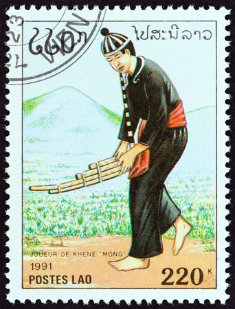 LAOS - CIRCA 1991: A stamp printed in Laos from the Traditional Music  issue shows  Mong player, circa 1991.