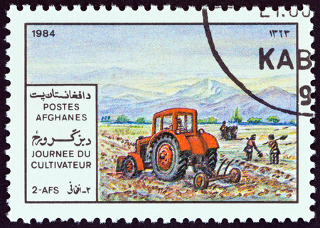 ploughing: AFGHANISTAN - CIRCA 1984: A stamp printed in Afghanistan from the Farmers Day  issue shows ploughing with Tractor, circa 1984. Editorial