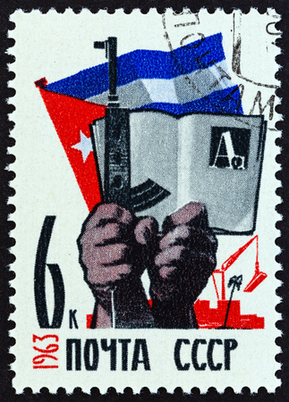 antique rifle: USSR - CIRCA 1963: A stamp printed in USSR from the Cuban-Soviet Friendship issue shows Hands, weapon, book and flag, circa 1963. Editorial