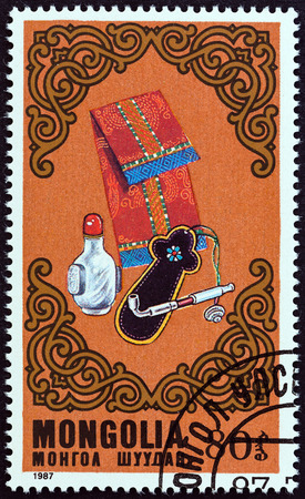 costume jewelry: MONGOLIA - CIRCA 1987: A stamp printed in Mongolia from the  Costumes and Costume Jewelry issue shows Pipe, pouch and bottle, circa 1987. Editorial