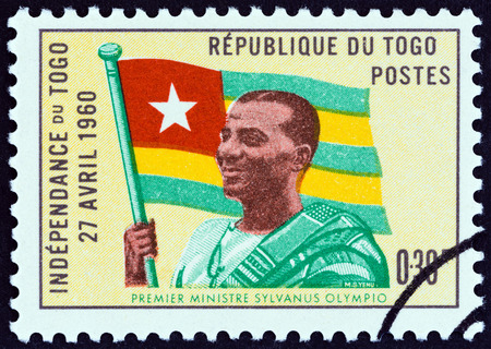 estampilla: TOGO - CIRCA 1960: A stamp printed in Togo from the Independence Commemoration issue shows Prime Minister Sylvanus Olympio and Flag, circa 1960.
