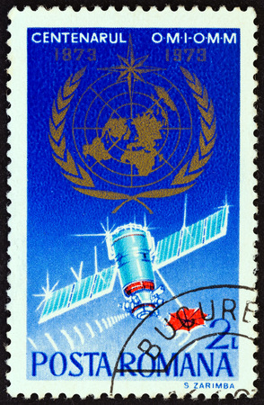 estampilla: ROMANIA - CIRCA 1973: A stamp printed in Romania from the 100th anniversary of the World Meteorological Organization issue shows emblem and weather satellite, circa 1973.