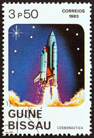cosmonautics day: GUINEA-BISSAU - CIRCA 1983: A stamp printed in Guinea-Bissau from the Cosmonautics Day issue shows Rocket carrying space shuttle, circa 1983.