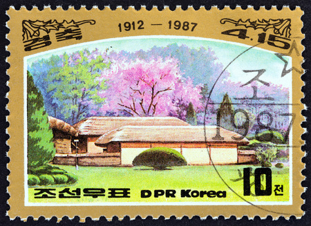 NORTH KOREA - CIRCA 1987: A stamp printed in North Korea from the The 75th anniversary of the Birth of Kim Il Sung, Paintings issue shows Kim Il Sungs birthplace, Mangyongdae, circa 1987.