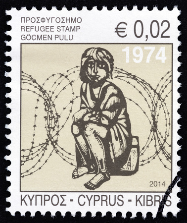 kibris: CYPRUS - CIRCA 2014: A stamp printed in Cyprus shows a child in front of barbed wire (wood engraving by A. Tassos), circa 2014.