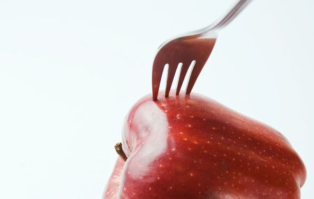 Red apple with a fork over white background