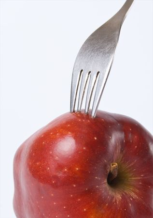 Red apple with a fork stuck in studio lighting conditions Stock Photo