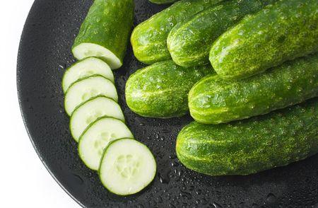 zucchini: pepinos y un pepino cortan en c�rculos, lavados y colocan en un plato de cer�mico negro aislado sobre fondo blanco