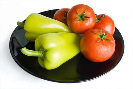 Fresh tomatoes and peppers washed and placed in a black ceramic plate isolated on white background