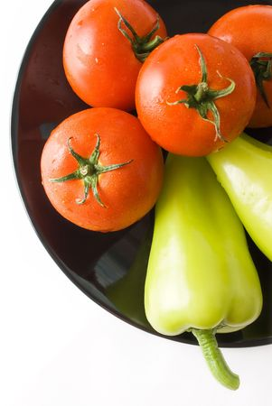 Tomatoes and peppers washed and placed in a black ceramic plate isolated on white background top view Stock Photo