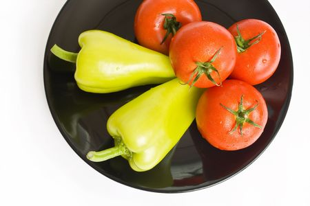 Tomatoes and peppers washed and placed in a black ceramic plate isolated on white background top view
