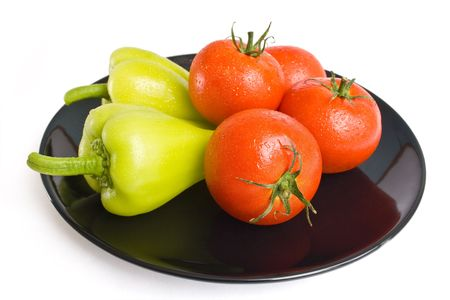 Tomatoes and peppers washed and placed in a black ceramic plate isolated on white background