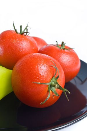 Tomatoes washed and placed in a black ceramic plate isolated on white background