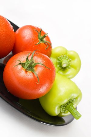 Fresh tomatoes and peppers washed and placed in a black ceramic plate isolated on white background Stock Photo
