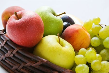 Various fresh ripe fruits close-up placed in a wicker basket Stock Photo
