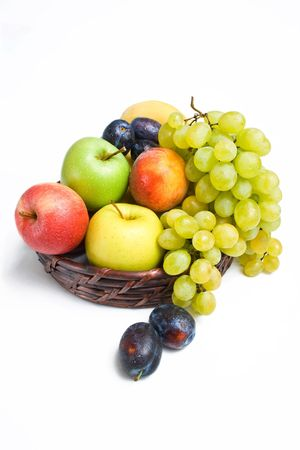 Ripe fruits placed in a wicker basket isolated on white background