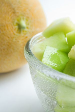 Portion of honeydew melon slices in a glass bowl on the background of whole fruit