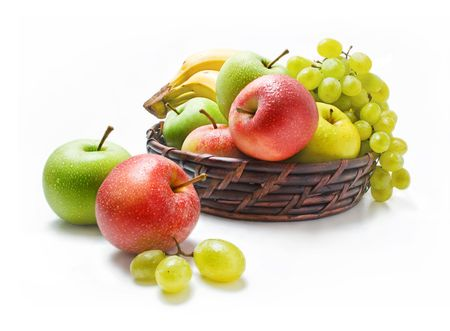Various fresh ripe fruits placed in a wicker basket and around isolated on a white background