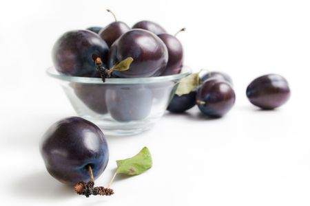 Fresh ripe plums in a glass bowl and around isolated on white background