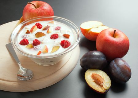 Glass bowl filled with yogurt mixed with fruit pieces arranged with spoon and some fruits around
