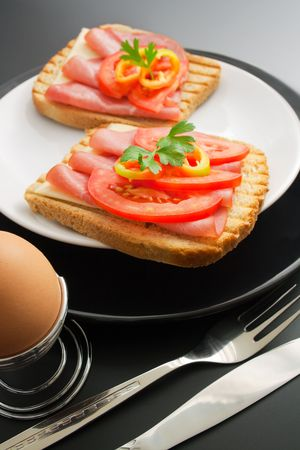 Breakfast. Pork tenderloin sandwiches, cheese, tomato and pepper arranged in ceramic plates in the company of soft-boiled egg placed in a special metal stand, fork and knife Stock Photo