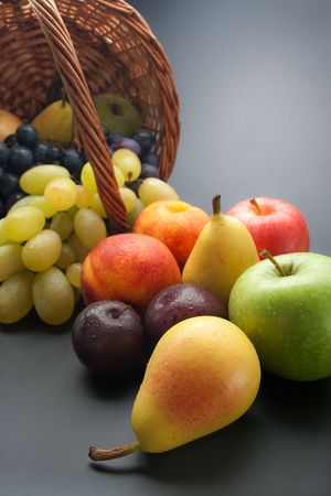 Fresh ripe fruits scattered from wicker basket on gray gradient background
