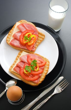 Breakfast. Pork tenderloin sandwiches, cheese, tomato and pepper arranged in ceramic plates in the company of soft-boiled egg placed in a special metal stand, fork, knife, spoon and glass of milk
