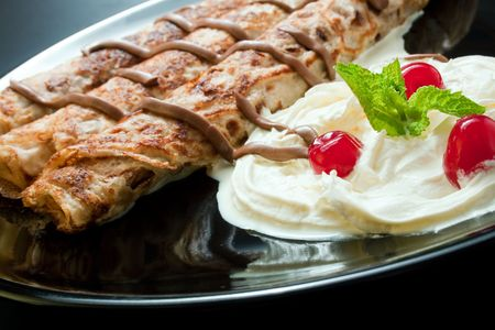 Pancakes close-up arranged with cream, cherries, chocolate and sprig mint leaves in black ceramic plate