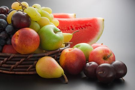 Various fresh ripe fruits placed in a wicker basket and around on gray gradient background photo
