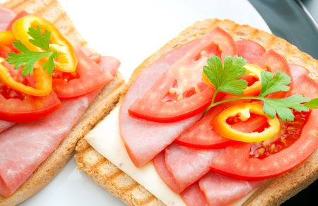 Fresh appetizing  sandwiches with pork tenderloin, cheese, tomato, pepper and parsley sprig arranged in ceramic plates.  Stock Photo