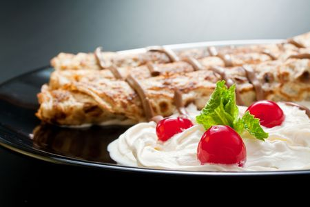 Three rolled pancakes close-up arranged with cream, cherries, chocolate and sprig mint leaves in black ceramic plate.