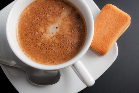 White porcelain cup of freshly brewed coffee close-up arranged with sandwich-biscuit, spoon and plate on dark gray background