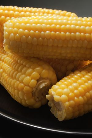 Freshly cooked corn close-up placed in a black ceramic plate Stock Photo