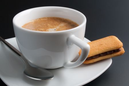 White porcelain cup of freshly brewed coffee arranged with plate, spoon and sandwich-biscuit with chocolate isolated on dark gray background photo