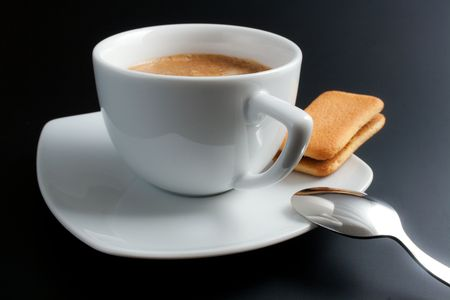 White porcelain cup of freshly brewed coffee close-up arranged with sandwich-biscuit spoon and plate on dark background