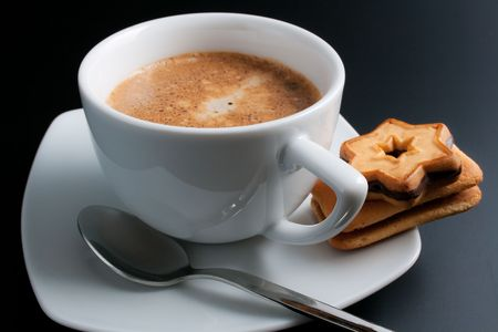 Coffee. White porcelain cup of freshly brewed coffee close-up arranged with two  sandwich-biscuits spoon and plate on dark background Stock Photo