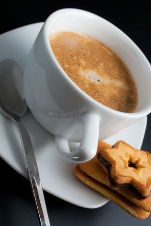 White porcelain cup of freshly brewed coffee close-up arranged with two sandwich-biscuits spoon and plate on dark background photo
