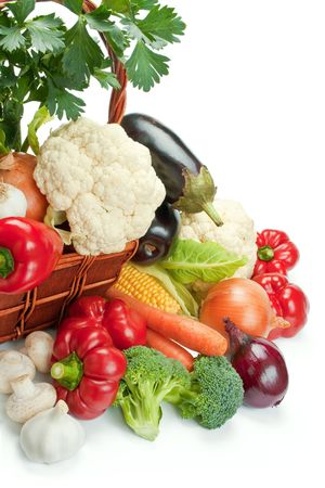 Mix of fresh ripe vegetables arranged in a wicker basket and around isolated on white background