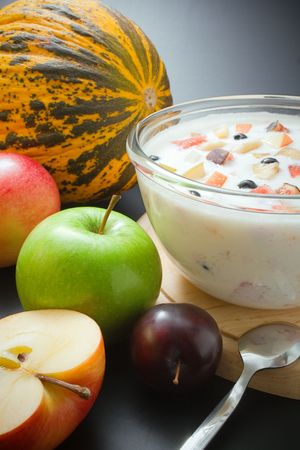 Fuits and yogurt. Glass bowl filled with yogurt mixed with fruit pieces arranged with spoon and some fruits around