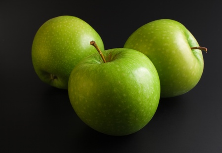 Apples. Three fresh ripe green apples close up arranged on dark background