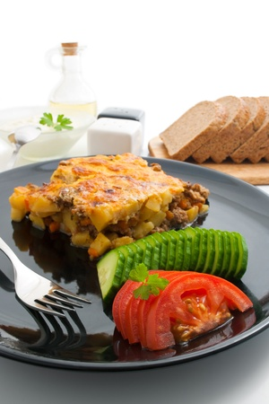 Moussaka.Traditional Bulgarian dish arranged in a black  plate with fresh sliced tomato and cucumber with a sprig of parsley, slices of bread, bowl of yogurt, a bottle with olive oil and containers for salt and pepper around isolated on a white background Stock Photo