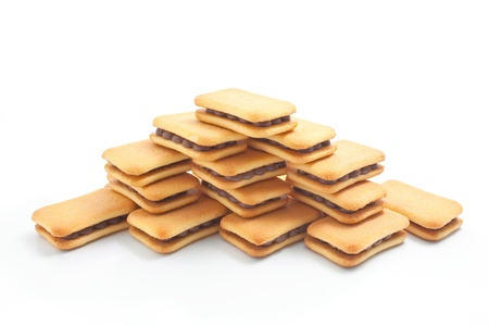 Sandwich biscuits with chocolate filling arranged in the shape of a pyramid isolated on white background Stock Photo