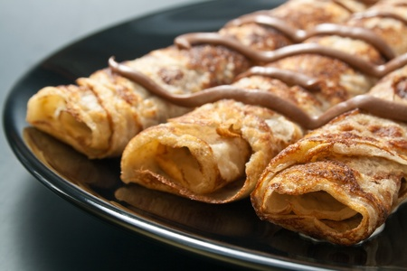 Pancakes. Freshly baked rolled pancakes with chocolate in a black ceramic plate